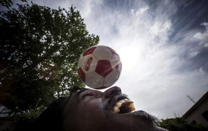 Un inmigrante juega al fútbol en el centro baobab de Roma.