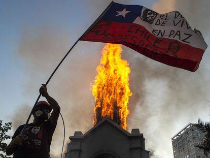 Un manifestante ondea una bandera chilena frente a una iglesia incendiada en Santiago, este domingo.