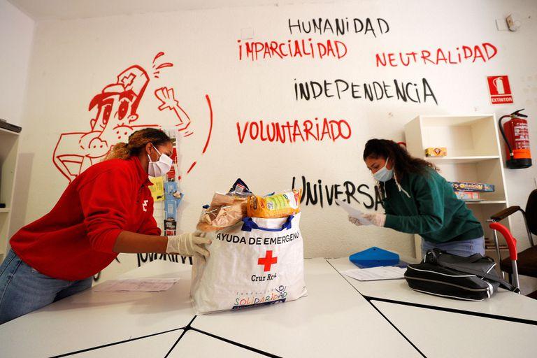 Una voluntaria de Cruz Roja entrega una bolsa con productos de primera necesidad a una joven.