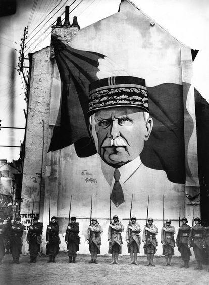 Una parada militar delante de un mural con el retrato del mariscal Pétain en Vichy durante la Segunda Guerra Mundial.