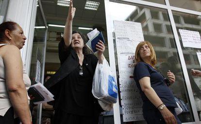 Unas mujeres aguardan en la entrada del Fondo de Salud Estatal para recibir medicamentos en Atenas.