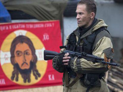 Un rebelde ucranio, ayer en Donetsk ante una bandera del Batallón Ortodoxo Ruso