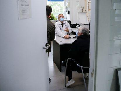 Un médico atiende a una paciente en el centro de salud Calesas en Usera en Madrid