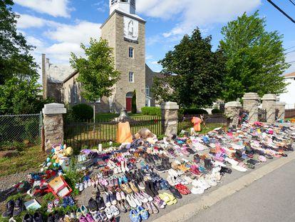 Flores y zapatos infantiles colocados frente a una iglesia en protesta tras el hallazgo de los restos de 215 niños en un orfanato.