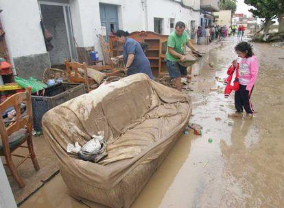 Vecinos de El Verger (Alicante) sacan los muebles de su casa, inundada por la crecida del río Girona.