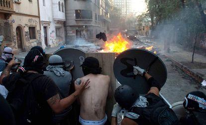 Un grupo de manifestantes se protegen con escudos improvisados en una protesta contra el Gobierno chileno.