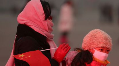 Una mujer y su hija, con mascarillas, cruzan la plaza de Tiananmen de Pekín el 30 de enero de este año.