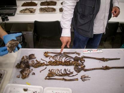 Dos investigadores ante los restos de una niña de cinco años de la Baja Edad Media hallados en la capilla del palacio gótico del Real Alcázar de Sevilla.