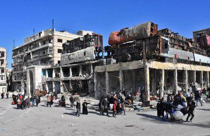 Sirios en un barrio reconquistado por las tropas sirias, este jueves