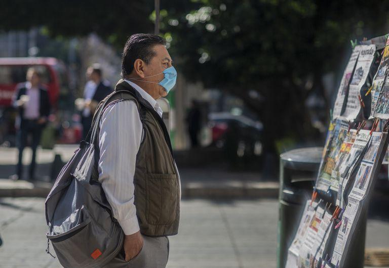 Un hombre, con un cubrebocas, mira los diarios en Ciudad de México.