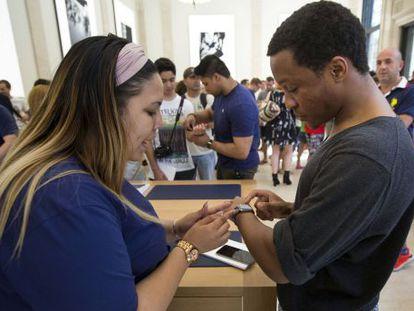 Una empleada de una de las tiendas de Apple en Nueva York prueba el reloj con un cliente.