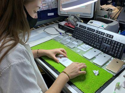 Una empleada de Smaaart comprueba el estado estético de unos móviles.