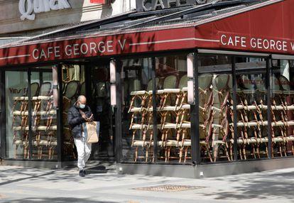 Un hombre, frente a un café cerrado en París.
