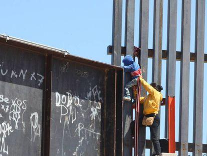 Una mujer ayuda a su hijo a trepar la valla fronteriza que divide a México y Estados Unidos.