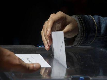 Un votante de Madrid introduce en la urna su voto.