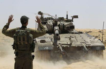 Un soldado israelí dirige las maniobras de un tanque junto a la frontera con Egipto.