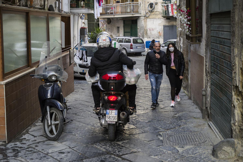 En la moto, Vincenzo y Antonio, voluntarios de la ONG Fondazione San Gennaro, reparten comida a los desfavorecidos, en el barrio Sanità de Nápoles.