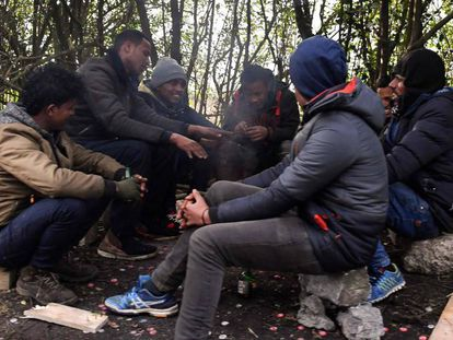 Un grupo de migrantes se calienta alrededor de un fuego, este viernes en Calais.
