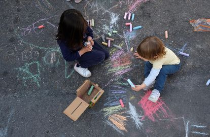 Dos niños juegan sobre el asfalto de la calle junto al colegio Asuncion Rincón en Madrid.