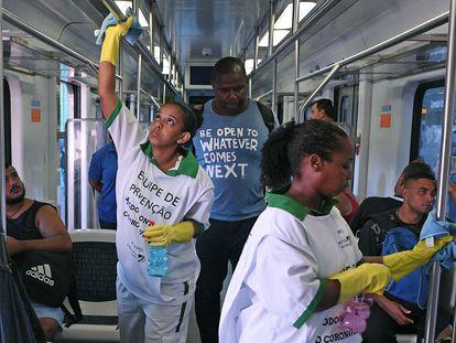 Dos trabajadoras desinfectan las barras de sujeción de un vagón de tren en Río de Janeiro.
