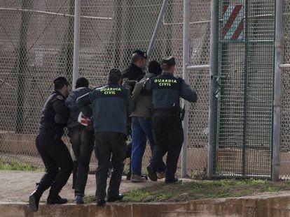 Agentes de la guardia civil expulsan por la valla de Melilla a un inmigrante en 2014.