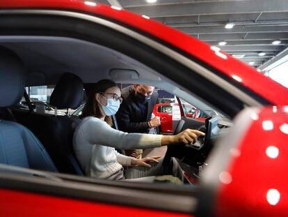Un vendedor muestra un vehículo a una clienta en un concesionario de Terrassa.