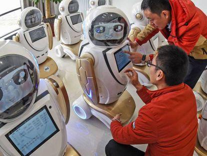 En foto, empleados de una fábrica de robots en una planta de la provincia de Jiangsu, China. En vídeo, acusaciones de espionaje por la detención de la vicepresidenta de Huawei.
