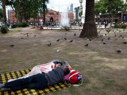 Una pareja duerme en la Plaza de Mayo, a las afueras de la Casa Rosada, en Buenos Aires.