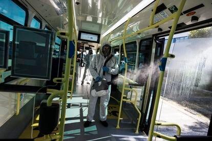 Un operario de la EMT desinfecta con un nebulizador un autobús de línea de la Empresa Municipal de Transportes de Madrid.