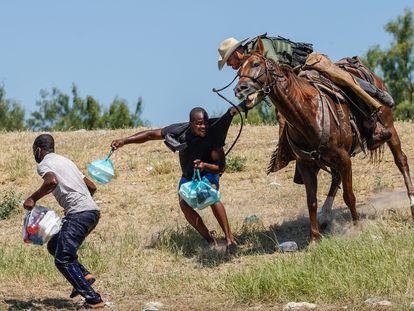 Un agente fronterizo de EE UU agarra a un migrante haitiano cerca del campamento de Del Río, Texas, este domingo.