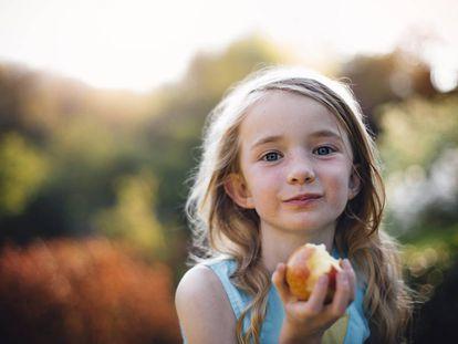 Una niña come una manzana.