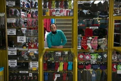 Manuel atiende una caseta de alquiler de trineos y esquís y de venta de guantes y gorros.