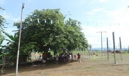 Un gran árbol cubre con su sombra de más de 10 metros tres mesas de contrachapado y hierro desgastadas y desconchadas en medio de un descampado. Donde hoy reciben clase 15 niños, antes había un vertedero de basura. Pulse en la imagen para ver la fotogalería completa.