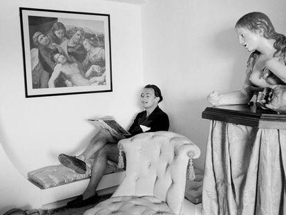 Salvador Dalí el 1951 en la biblioteca de Portlligat, leyendo bajo un fragmento de 'Traslado de Cristo', pintado por Rafael el 1507.