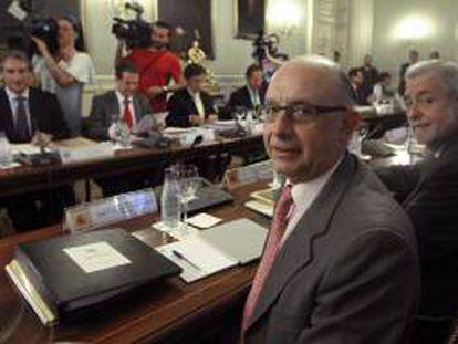 El ministro de Hacienda y Administraciones Públicas, Cristóbal Montoro (2d), junto al secretario de Estado de Administraciones Públicas, Antonio Beteta (d), durante la reunión de la Comisión Nacional de Administración Local.