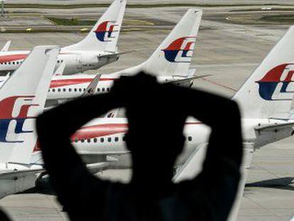 Un hombre mira un avión de Malaysia Airlines en el aeropuerto de Kuala Lumpur, el pasado 25 de febrero.