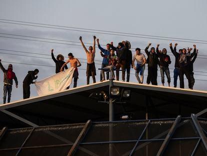 Un grupo de internos pide su liberación en el tejado del CIE de Aluche (Madrid), este martes.