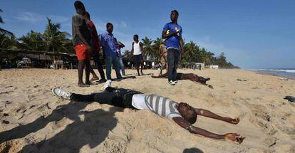 Vecinos de Grand Bassam se acercan a los cuerpos de algunos de las víctimas del ataque armado en un hotel de la ciudad costamarfileña, el pasado 13 de marzo.