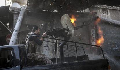 Un combatiente rebelde dispara una ametralladora contra las fuerzas del régimen en el barrio alepino de Jedida.