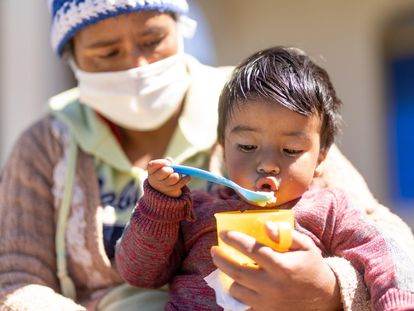 Erick Samuel, de 18 meses, come albaricoques, en Guatemala.