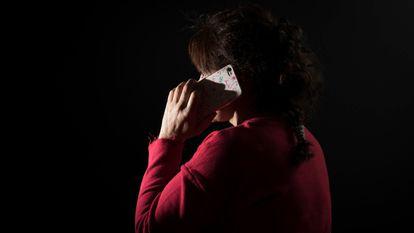 Una mujer víctima de maltrato habla por su teléfono móvil.