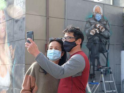 Dos personas se toman una foto junto a un mural del senador Bernie Sanders en Culver City, California.