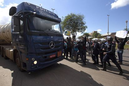 Policías escoltan la salida de camiones con combustible de la distribuidora de Petrobras.