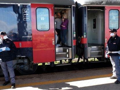 Pasajeros italianos en un tren saliendo de Milán.
