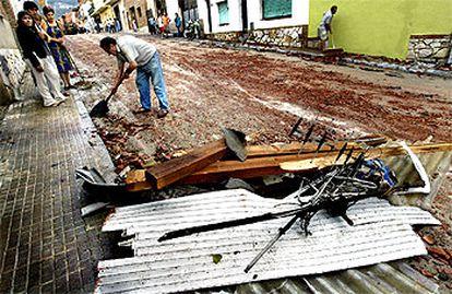 Vecinos  de Centelles limpian el barro y los cascotes de la calle tras la turbonada que ayer afectó el sur de Osona.