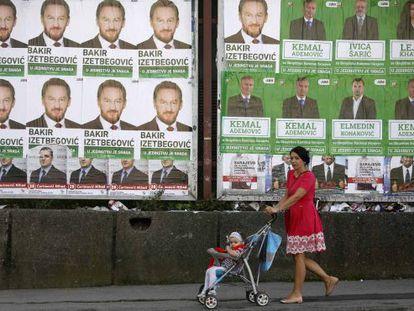 Una mujer pasa con una niña ante carteles electorales en Sarajevo.