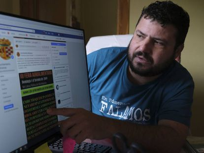 El alcalde de Bimenes (Asturias), Aitor García, muestra en su despacho una publicación en asturiano en el Facebook del Ayuntamiento.
