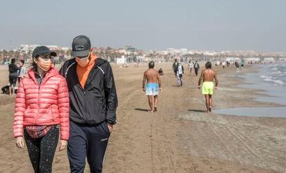 Varias personas pasean por la playa en Valencia el 31 de marzo.