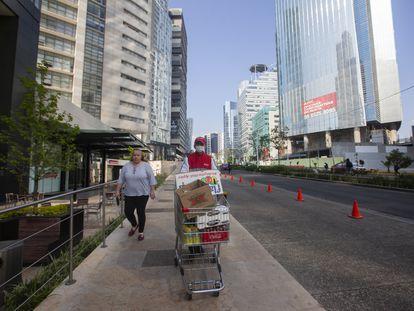 Un empleado de supermercado lleva la compra de un cliente en la zona de Santa Fe.