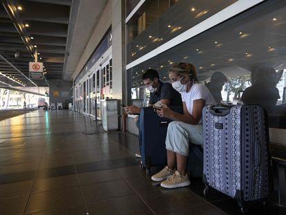 Una pareja usa sus móviles frente a las puertas de ingreso del aeropuerto de vuelos domésticos  Jorge Newbery, en Buenos Aires, el pasado 20 de marzo.